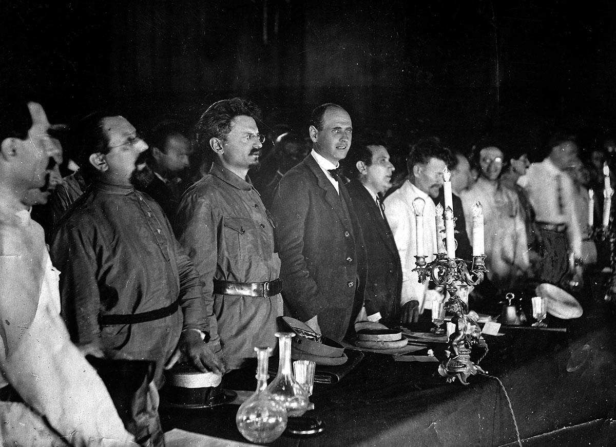 Лев Троцкий (третий слева) в президиуме III Конгресса Коммунистического Интернационала. В президиуме были также Григорий Зиновьев, Михаил Калинин, Карл Радек, Николай Бухарин, Лев Каменев. Из них впоследствии уцелел только Калинин, Петроград, 1921 год